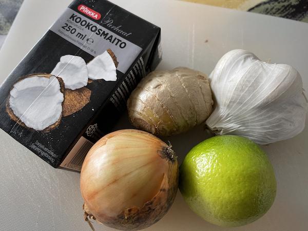 Kookosmaito, sipuli, inkivääri, lime ja valkosipuli leikkuulaudalla